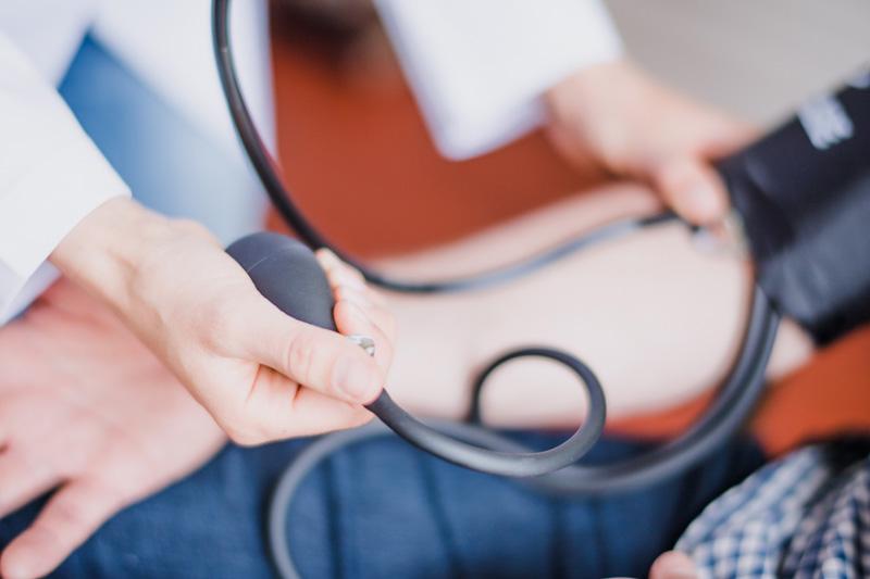Lekarz mierzący ciśnienie pacjentowi orazbadający puls przy ucisku ramienia